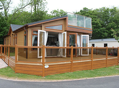 AB Sundecks Picket Glass, Decking and Steps surrounding a Lodge with a balcony on top with Steel Top Glass and stairs